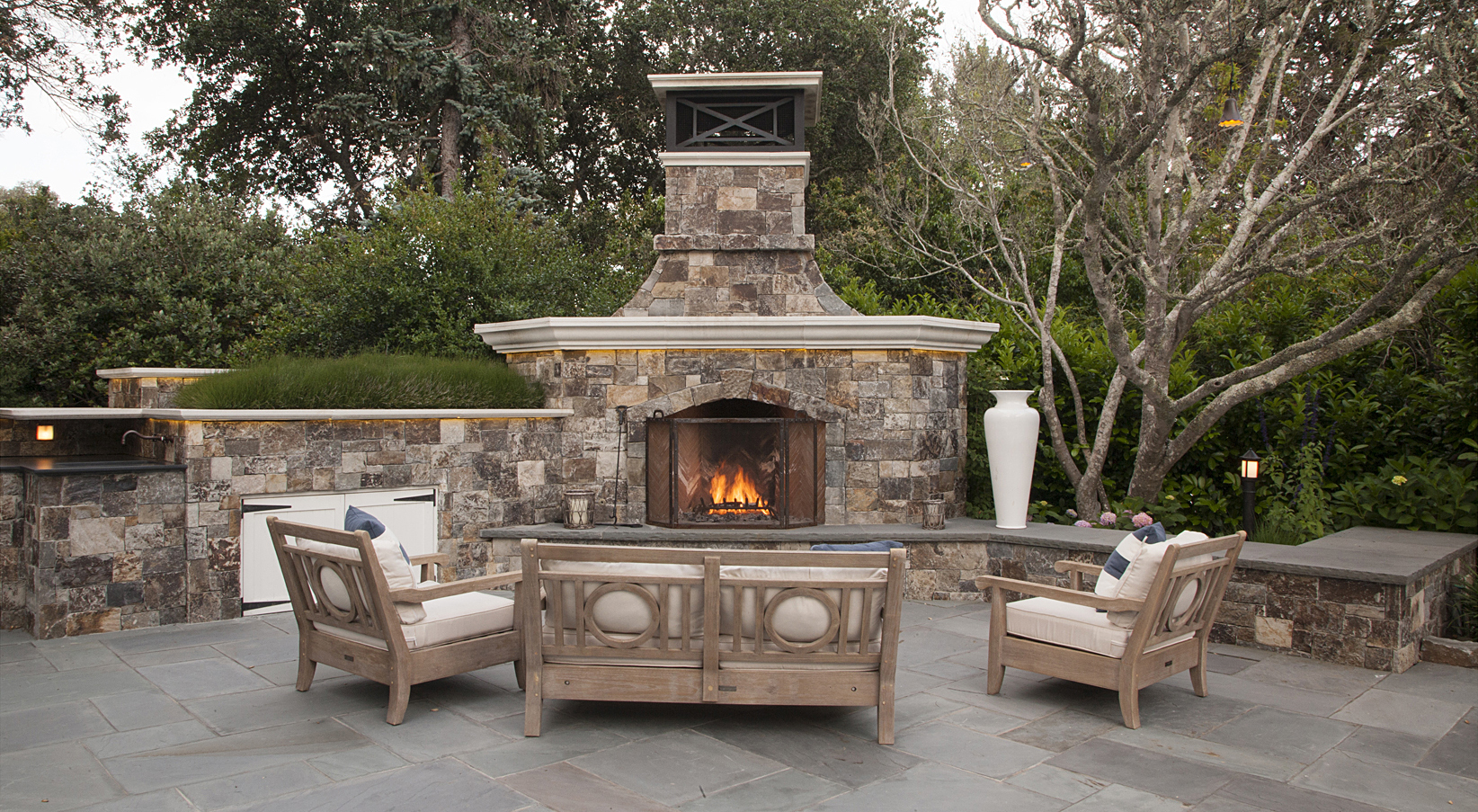 Custom-designed stacked-stone fireplace anchors an outdoor living area. Northern California residential landscape. Design: Simmonds & Associates
